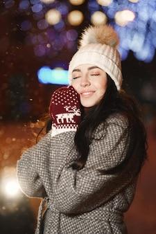 通りで若い女性の屋外の夜の肖像画