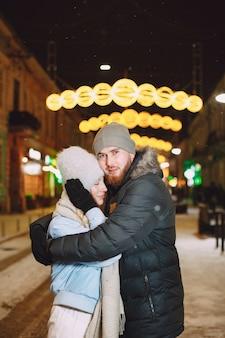 Ritratto notturno all'aperto di giovani coppie che posano in strada