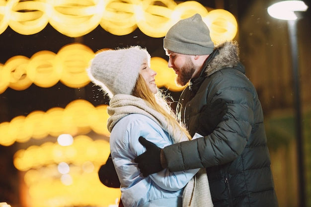 Outdoor night portrait of young couple posing in street