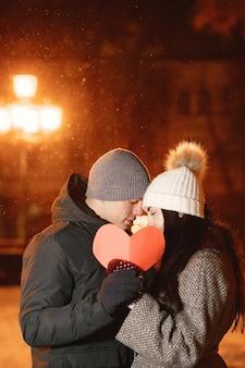 Ritratto notturno all'aperto di giovani coppie con cuore di carta in strada