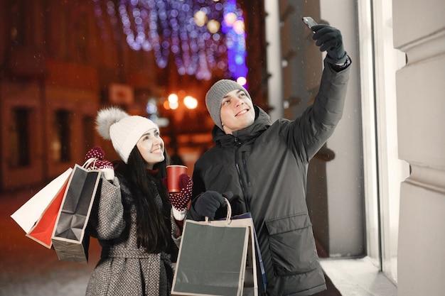 Ritratto notturno all'aperto di giovani coppie con borse della spesa