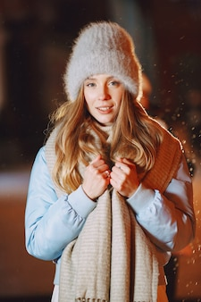 Outdoor night portrait of young woman posing in street
