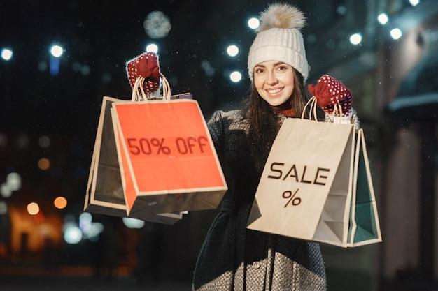 Ritratto notturno all'aperto di giovane donna con borse della spesa