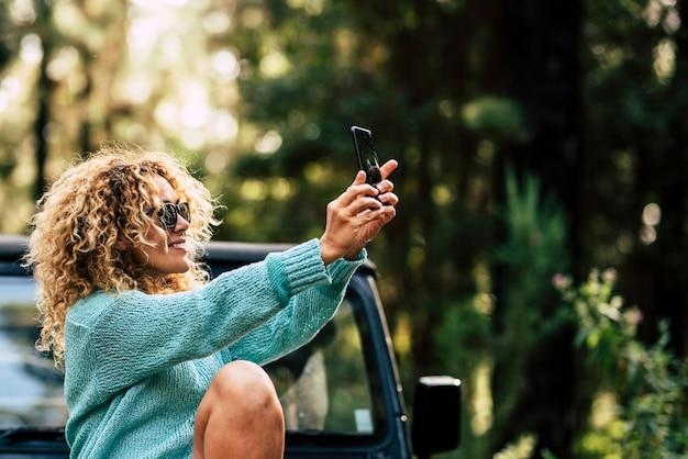 屋外の人々は、陽気な白人女性が車で旅行中に森の中でスマートフォンで写真を撮るというテクノロジーを楽しんでいます-大人の女性と自然との代替休暇