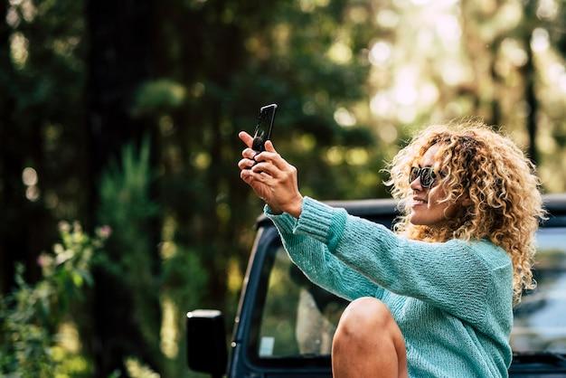 アウトドアの人々は、陽気な白人女性が車で旅行中に森の中でスマートフォンで写真を撮る技術を楽しんでいます