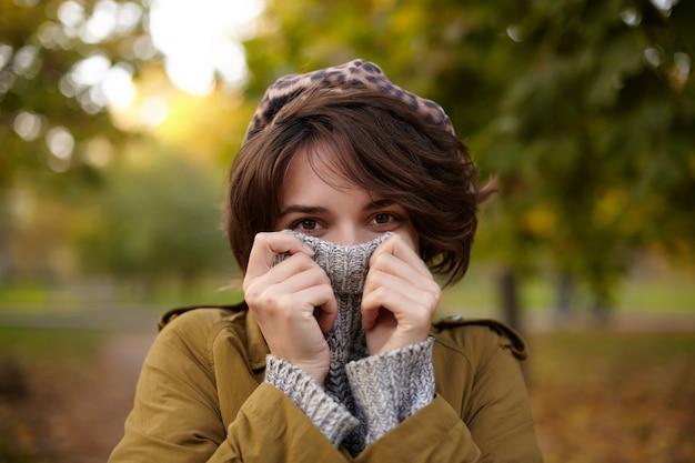 Foto all'aperto di attraente giovane femmina bruna dagli occhi marroni con trucco naturale che indossa vestiti alla moda mentre posa sul parco sfocato e nasconde il viso