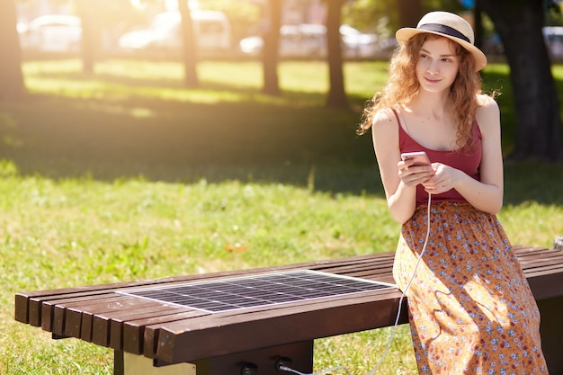 Outdoor photo of attractive woman with wavy hair, wearing hat, floor skirt and casual r shirt, sitting on bench in park
