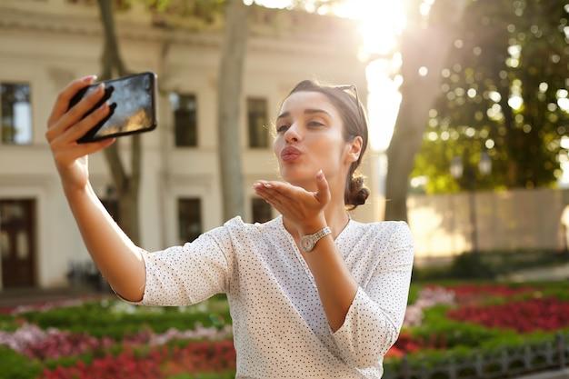Foto all'aperto di attraente giovane donna bruna con acconciatura panino che invia bacio d'aria mentre fa selfie con lo smartphone, in piedi sopra l'ambiente urbano in una calda giornata luminosa