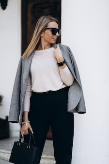 Outdoor photo of blonde lady posing on architecture background in autumn day. fashion street style portrait. wearing dark casual trousers and creamy sweater and sunglasses. fashion concept.