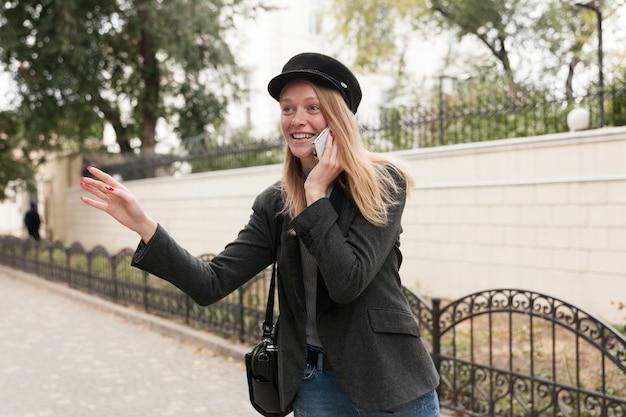 Foto all'aperto di affascinante giovane femmina bionda positiva in abiti alla moda alzando la mano in gesto di ciao e sorridendo felicemente mentre si effettua una chiamata con il suo smartphone