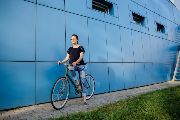 Outdoor photo of cheerful girl in sunglasses standing with bike against the blue building. dressed up in stylish casual clothes.