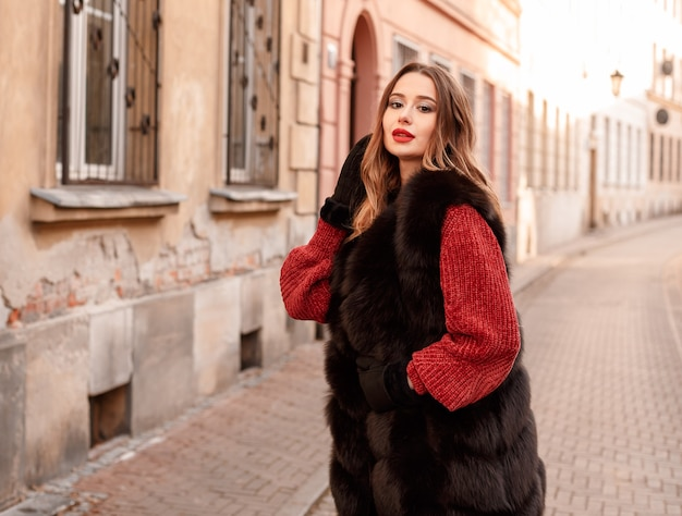 Outdoor photo of fashionable female model walking around city in winter vacation.