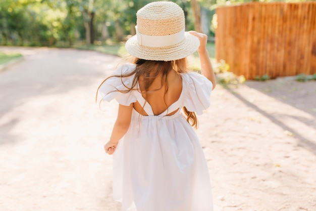 Outdoor photo from back of little girl with tanned skin standing on the street in sunny morning. charming female kid wears straw hat decorated with ribbon and white dress dancing in park.