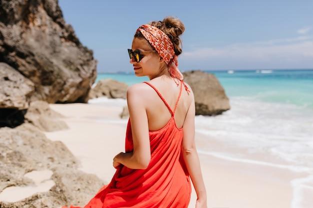 魅力的な日焼けした女の子の後ろからの屋外写真は、流行のリボンを着ています。海の近くの野生のビーチでリラックスした赤いドレスを着た壮大な若い女性の肖像画。