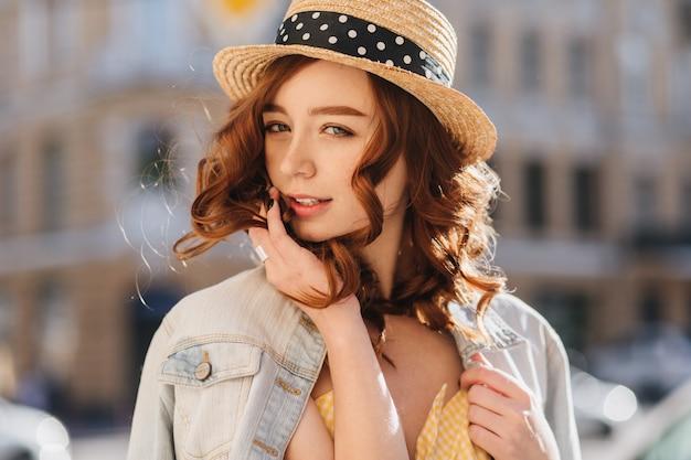Foto all'aperto della splendida signora caucasica con i capelli rossi in giro per la città. modello femminile alla moda in cappello di paglia in posa con piacere in una giornata calda.