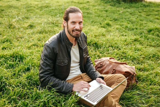 Outdoor photo of handsome stylish guy in leather jacket looking at you, while sitting on grass in green park and using silver notebook