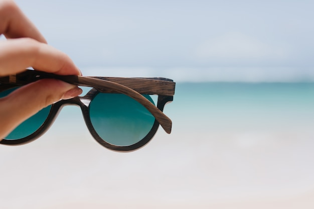 Outdoor photo of ocean with female hand on foreground. woman holding summer sunglasses on sea.