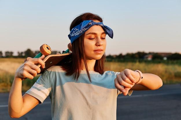 티셔츠와 헤어밴드를 한 아름다운 브루네트 여성이 스케이트보드를 타는 동안 손목시계를 바라보고 있는 야외 사진은 롱보드를 어깨에 들고 집중된 표정입니다.