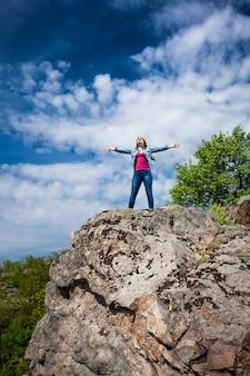 손을 뻗어 높은 절벽 꼭대기에 서있는 아름다운 여인의 야외 사진