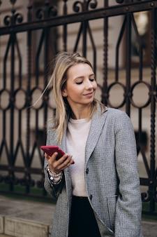 秋の日のアーキテクチャの背景にポーズをとってブロンドの女性の屋外の写真。携帯電話を保持しているファッションストリートスタイルの肖像画を閉じます。ダークカジュアルなズボン、クリーミーなセーター、グレーのコートまたはジャケットを着ています。