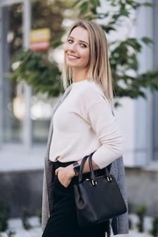 秋の日のアーキテクチャの背景にポーズをとってブロンドの女性の屋外の写真。ファッションストリートスタイルのportrait.wearing暗いカジュアルなズボン、クリーミーなセーター、グレーのコートまたはジャケットを閉じます。ファッションのコンセプトです。