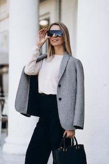 秋の日のアーキテクチャの背景にポーズをとってブロンドの女性の屋外の写真。ファッションストリートスタイルの肖像画。暗いカジュアルなズボンとクリーミーなセーターとサングラスを着ています。ファッションのコンセプトです。