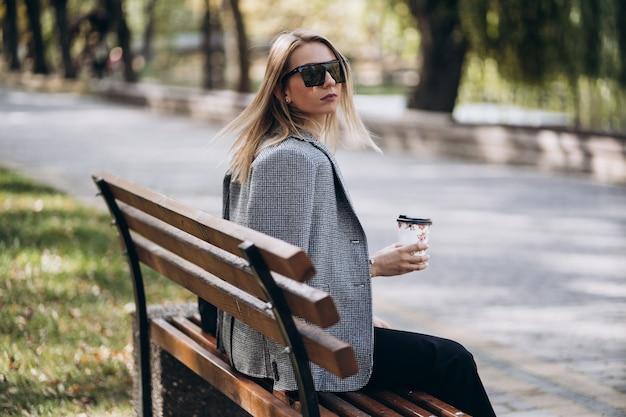 Наружное фото белокурой дамы с кофе, сидя на скамейке в осенний день. уличный стиль моды. в темных повседневных брюках, кремовом свитере и солнечных очках. концепция моды и отдыха.