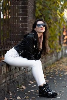 갈색 머리 아가씨의 야외 사진 이을 날에 울타리에 앉아. 패션 스트리트 스타일 초상화. 흰색 바지, 티셔츠, 검은 가죽 자켓, 선글라스 및 검은 모자를 착용하는 소녀. 패션, 긴장 개념.