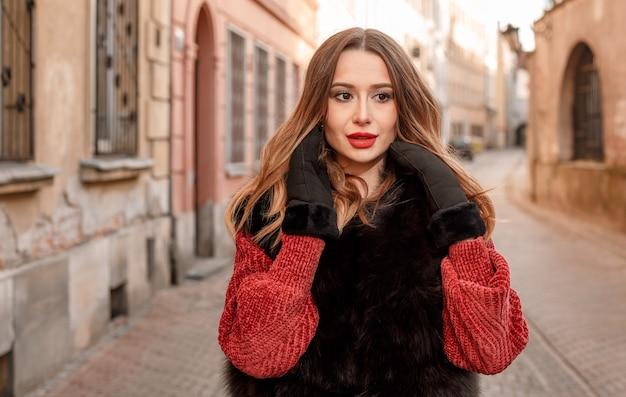 겨울 방학에 도시 주위를 산책하는 유행 여성 모델의 야외 사진.