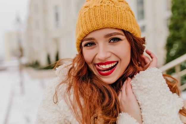 Напольное фото игривой женщины имбиря наслаждаясь зимой. смеющаяся обаятельная дама в желтой шляпе гуляет на открытом воздухе.