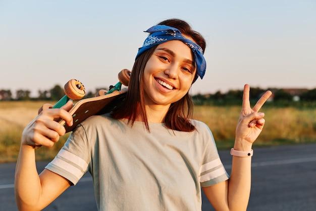 예쁜 브루네트 여성이 티셔츠와 헤어밴드를 입고 이빨 미소로 카메라를 바라보고 엄지손가락을 치켜들며 긍정적인 감정을 표현하는 야외 사진.
