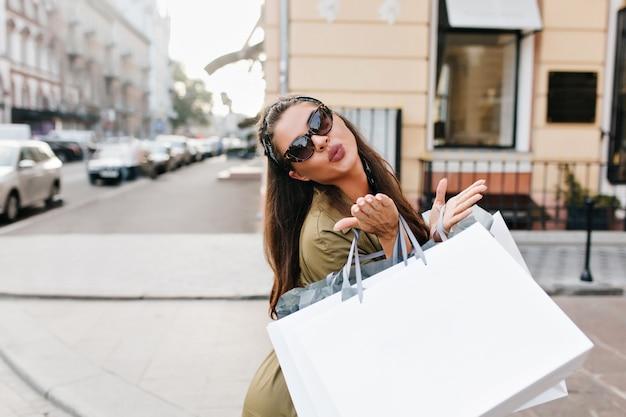 낭만적 인 장발 여성 모델의 야외 사진은 쇼핑하는 동안 공기 키스를 보냅니다.