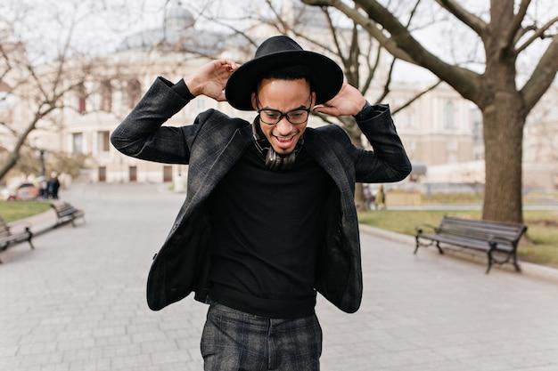 春の公園で楽しんでいるスリムなアフリカ人の屋外写真。通りで踊っている帽子をかぶった熱狂的なブルネットの黒人男の肖像画。