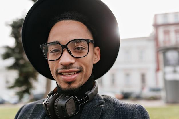 큰 모자 포즈에서 웃는 아프리카 젊은 남자의 야외 사진. 공원에서 시간을 보내는 검은 헤드폰에 재미있는 남자의 클로즈업 초상화.