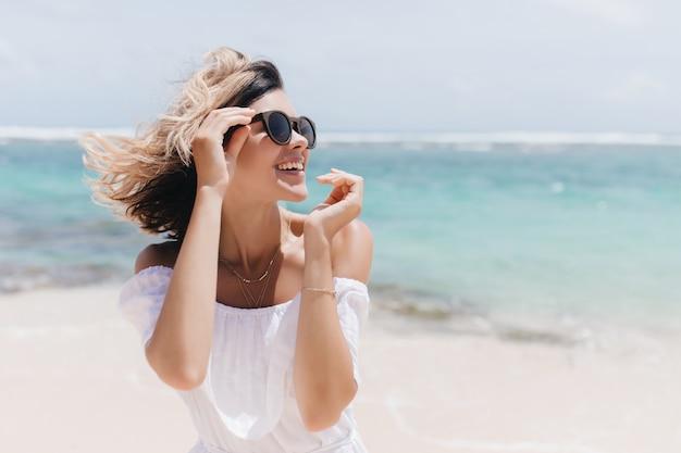 리조트에서 포즈를 취하는 짧은 헤어 스타일로 웃는 영감을 된 여자의 야외 사진. jocund 무두질 백인 여자 바다 해안에 웃 고.
