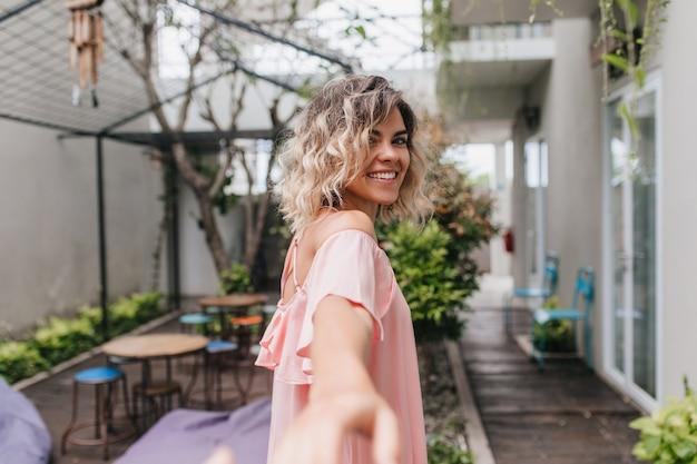 Наружное фото чудесной белокурой девушки, оглядывающейся через плечо. вдохновленная коротковолосая европейская женщина в розовом наряде стоит возле уличного ресторана.