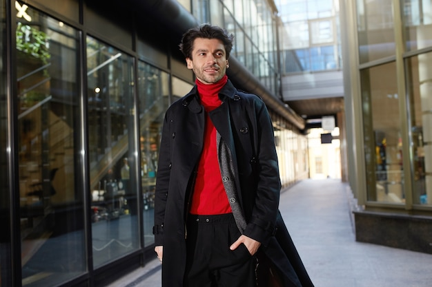 都会の背景の上に立っている間、赤いロールネックのセーターと黒いトレンチを身に着けているトレンディなヘアカットを持つ若い魅力的な黒髪の男性の屋外写真