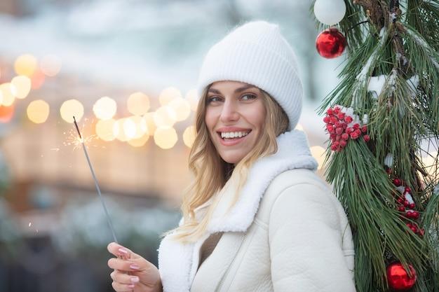 Наружное фото молодой красивой счастливой улыбающейся девушки, держащей бенгальский огонь, идущей по улице. женщина в стильной зимней одежде. рождество, новый год, концепция.
