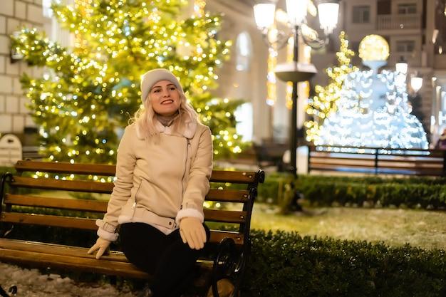 폭죽을 들고 거리에서 포즈를 취하는 젊은 아름 다운 행복 웃는 소녀의 야외 사진. 배경에 축제 크리스마스 박람회입니다. 세련된 겨울 코트, 니트 비니 모자, 스카프를 착용한 모델.