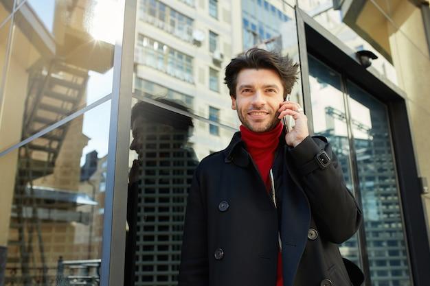 スマートフォンで電話をかけ、心地よい笑顔でカメラを前向きに見ている流行の服を着た若いかなり剃っていないブルネットの男の屋外写真
