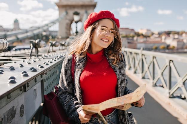 Foto all'aperto di bella donna che viaggia in bicchieri tenendo la mappa sul ponte della città