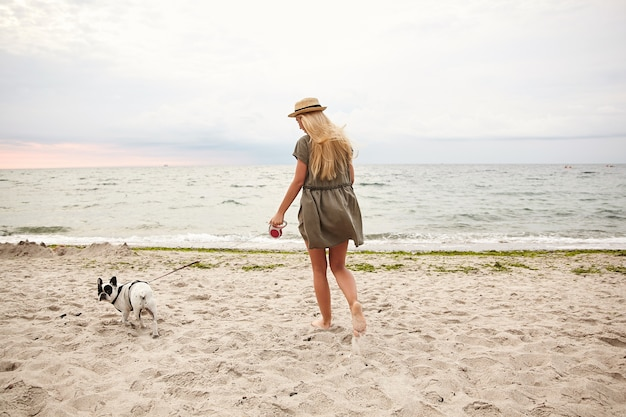 Outdoor photo of slim young female with long blonde hair wearing summer dress and boater hat, keeping her dog on leash while walking along beach on gray cloudy day