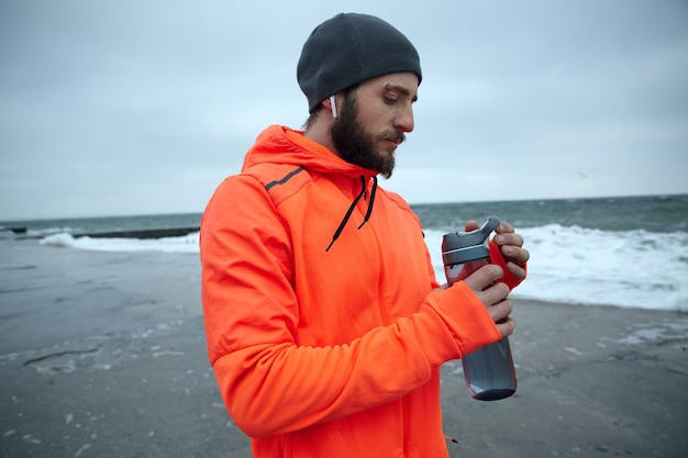 Outdoor photo of sporty young bearded male in black cap and warm orange coat with hood keeping fitness bottle in his hands while walking over seaside after morning run