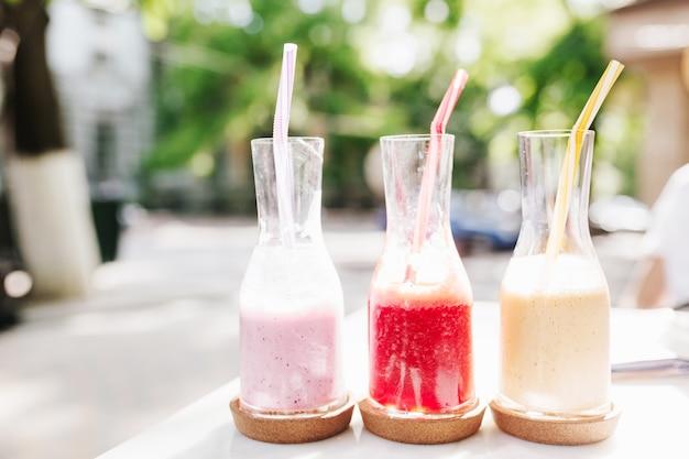 Foto all'aperto di tre bottiglie di gustosi cocktail di frutta