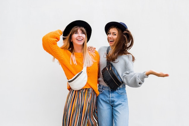 Una foto all'aperto di due amici femminili allegri che passano insieme grande momento che posa sul bianco
