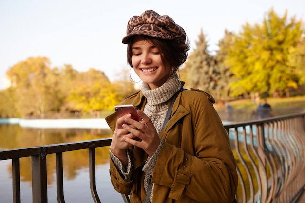 Outdoor photo of young attractive short haired brunette female dressed in stylish clothes holding mobile phone in raised hands and looking cherfully on screen, waiting for her friends in city garden
