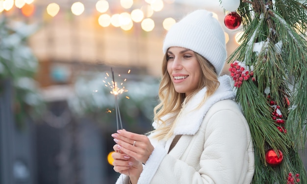 Outdoor photo of young beautiful happy smiling girl holding sparkler, walking on street. woman wearing stylish winter clothes. christmas, new year, concept.