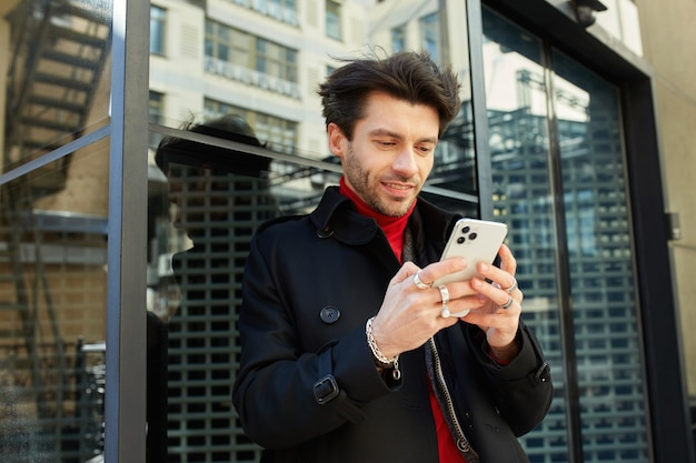 Outdoor photo of young brown haired unshaved guy keeping mobile phone in raised hands and looking positively on screen while standing over city background