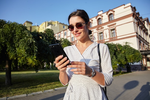 Outdoor photo of young cheerful dark haired lady in white polka-dot dress holding mobile phone while walking along city during lunch break, smiling while looking on screen