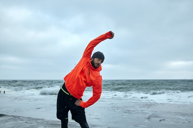 Outdoor photo of young dark haired bearded sportsman posing over seafront in cold early morning, raising hand while making stretching before running long distance along seaside